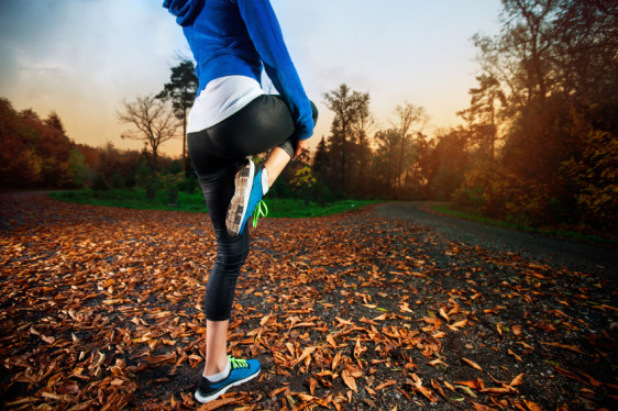 Young woman stretching before running in the early evening in th