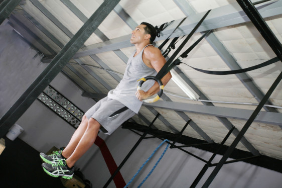 Young gymnast training on rings