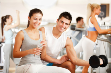 Beautiful couple spends time together at  gym. They doing exercise
