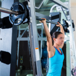 brunette girl in multipower barbell shoulder press Smith machine